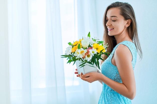 Linda caucasiana alegre feliz jovem sorridente com flores coloridas brilhantes e decorativas.