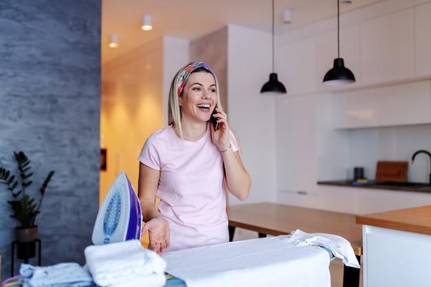 Linda caucasiana digna jovem loira dona de casa ao lado de tábua com roupa e falando ao telefone.