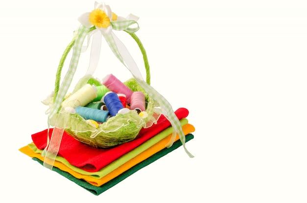 Linda cesta de vime com carretéis de linha multicoloridos fica em pedaços de tecido multicolorido.