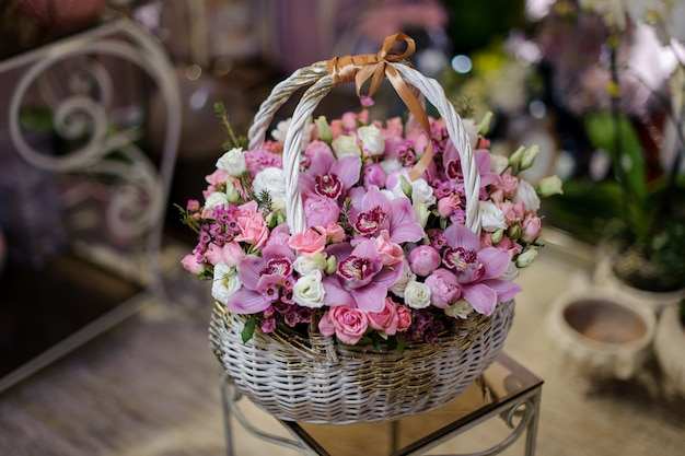 Linda cesta vintage branca de orquídeas cor de rosa e rosas