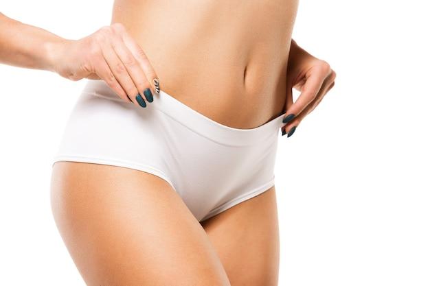 Linda cintura feminina e barriga isolada no fundo branco.
