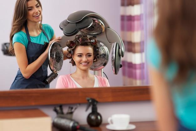 Linda cliente sentada sob o secador de cabelo com rolos