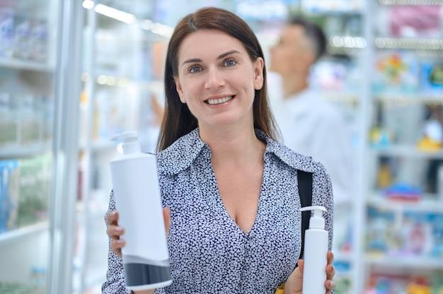 Linda cliente sorridente e alegre com dois frascos de bomba de plástico nas mãos, parada na farmácia