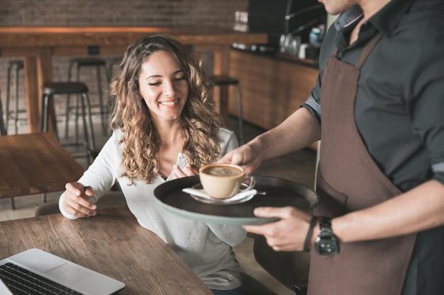 Linda cliente tão feliz recebendo seu café servido pela garçonete no café