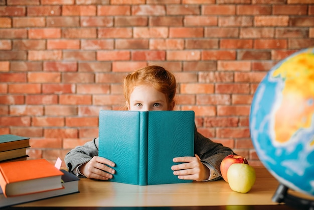 Linda colegial com livros didáticos posa na mesa.