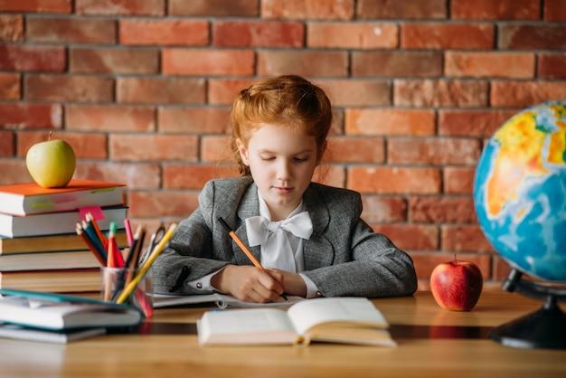 Linda colegial fazendo lição de casa na mesa