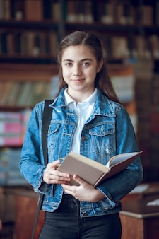Linda colegial na biblioteca lendo um livro, educação