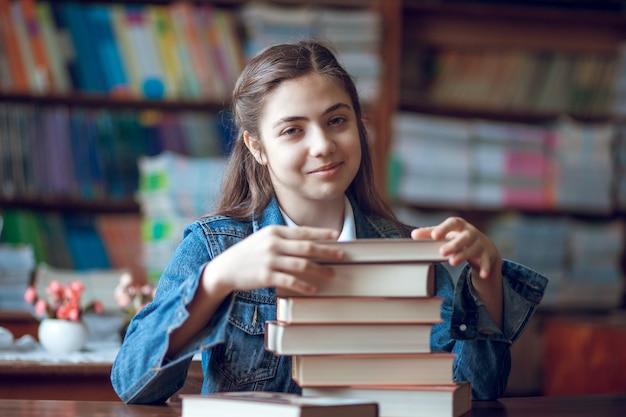 Linda colegial sentada na biblioteca com livros, educação