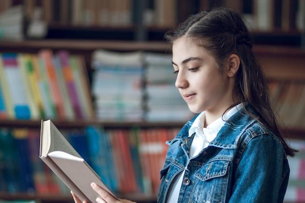 Linda colegial sentada na biblioteca lendo um livro, educação
