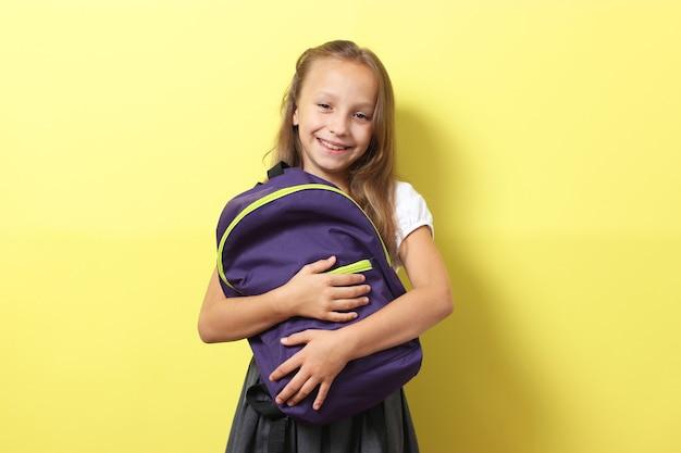 Linda colegial sorridente com uma mochila escolar em um fundo colorido