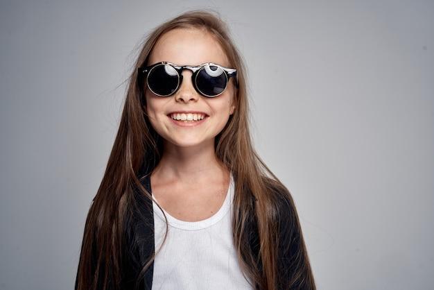 Linda colegial usando óculos escuros isolados