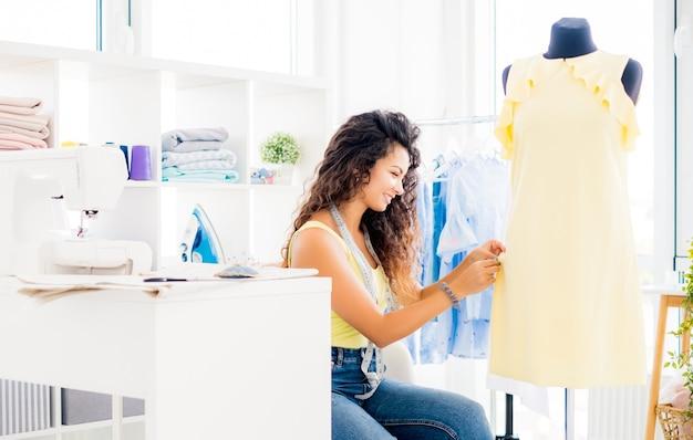 Linda costureira ajustando vestido em manequim na oficina