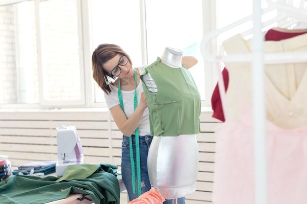 Linda costureira de óculos com fita métrica faz uma blusa verde com a ajuda de um manequim de alfaiate e alfinetes. conceito de oficina de costura própria.