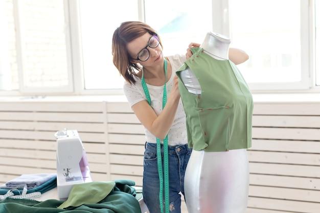 Linda costureira de óculos com uma fita métrica faz uma blusa verde com a ajuda