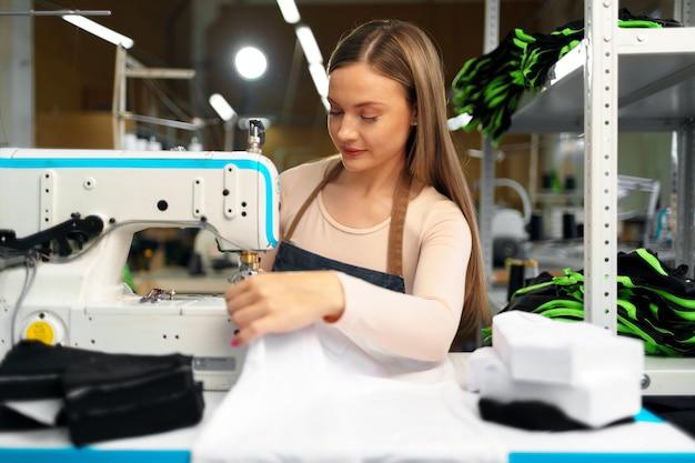 Linda costureira trabalhando com tecido em seu local de trabalho na fábrica de têxteis