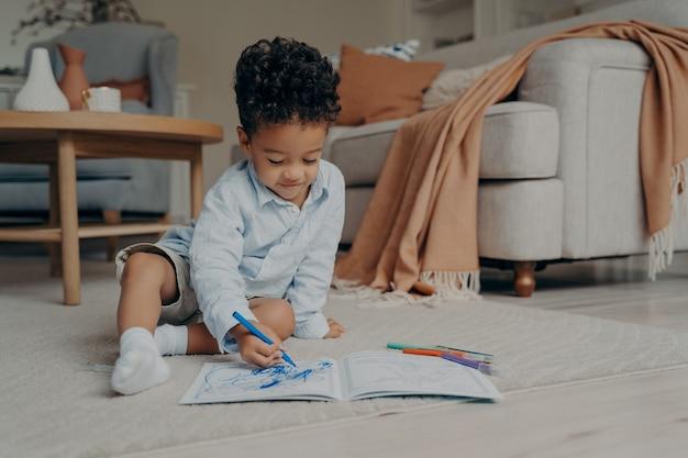 Linda criança africana sentada no chão e desenhando enquanto brinca em casa