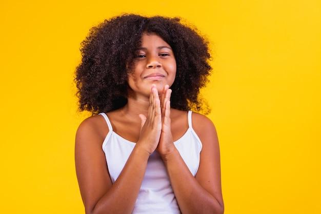 Linda criança afro-americana com as mãos juntas em gesto de oração, expressando esperança e por favor o conceito. menina brasileira com cabelo encaracolado.