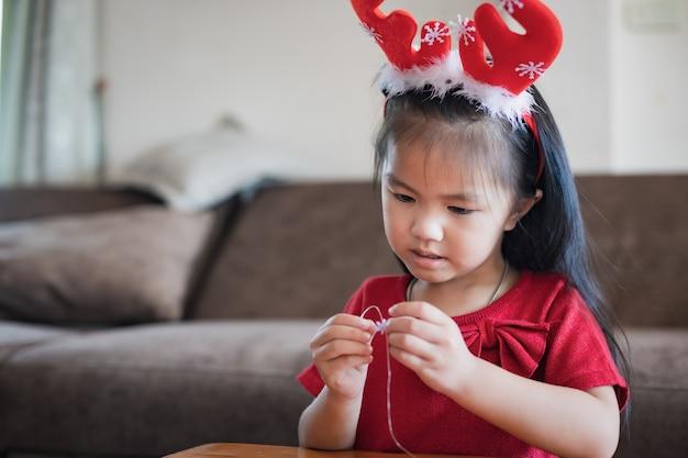 Linda criança asiática com fantasia de natal enfiando miçangas em uma corda com intenção e diversão em casa.