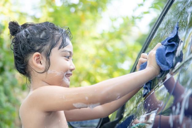 Linda criança asiática lavando um carro com mangueira num dia de verão