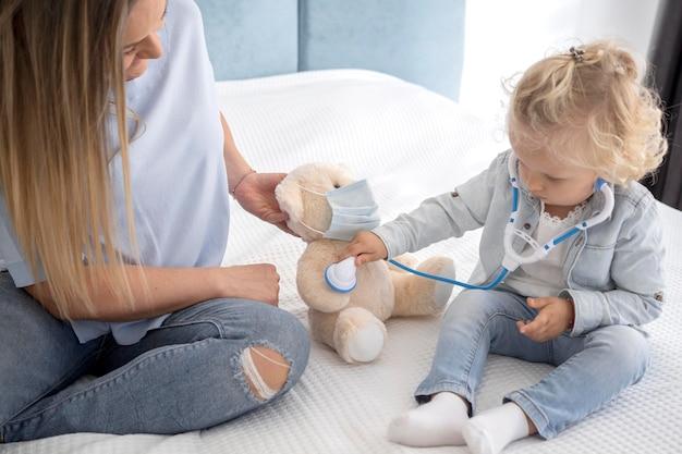 Linda criança brincando com um brinquedo e estetoscópio em casa durante a quarentena