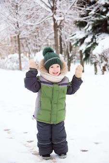 Linda criança brincando na neve. atividades de inverno para crianças.
