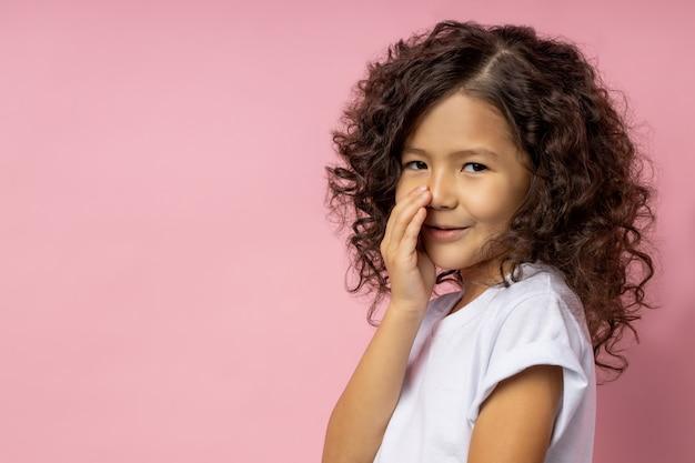 Linda criança caucasiana vestida com uma camiseta branca, cobrindo a boca com a mão e contando um segredo