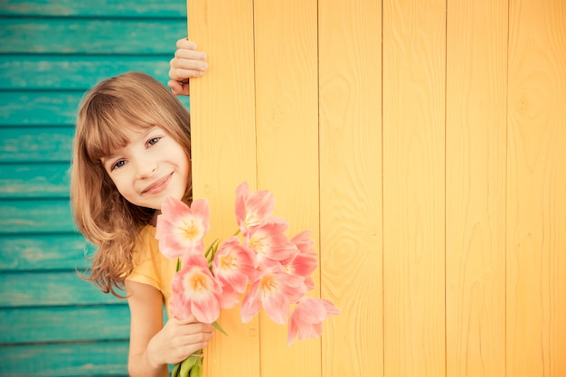 Linda criança com buquê de flores escondido atrás do conceito de dia das mães com fundo de madeira