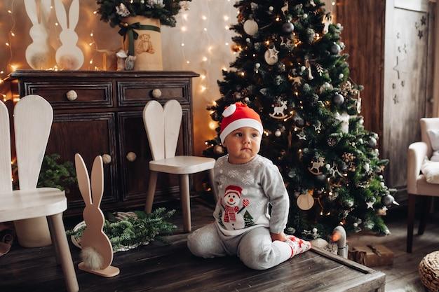 Linda criança com chapéu de papai noel e pijama sentada no chão de madeira perto da árvore de natal