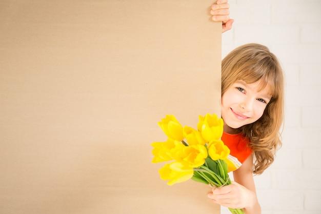 Linda criança com um buquê de flores escondido atrás da bandeira em branco feriado familiar dia das mães