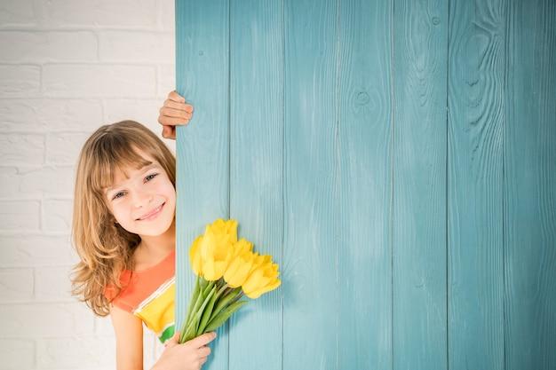 Linda criança com um buquê de flores escondido atrás de um fundo de madeira.
