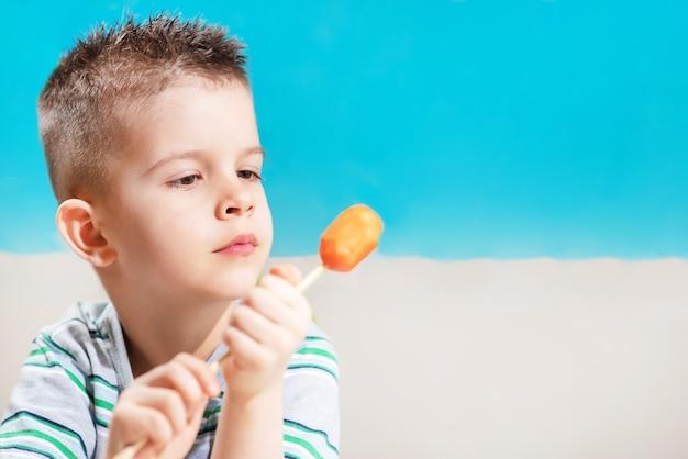 Linda criança come cenoura fresca no espeto. rapaz rói vegetais em um fundo azul.