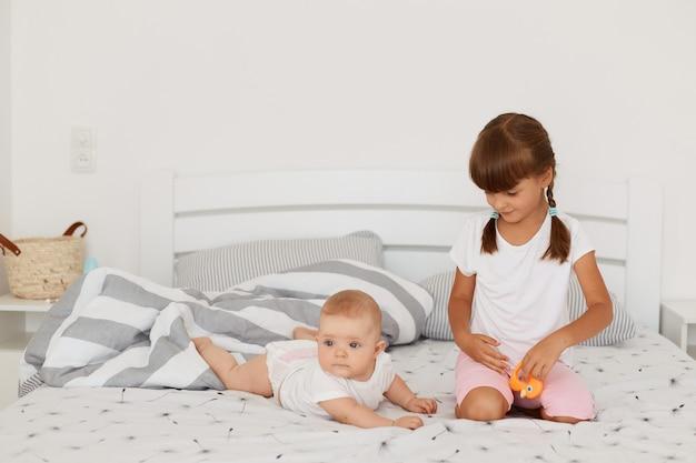 Linda criança de cabelos escuros com rabo de cavalo sentado na cama perto de sua irmã infantil, posando no quarto claro, a menina mais velha, olhando para o bebê encantador, passando um tempo juntos em casa.
