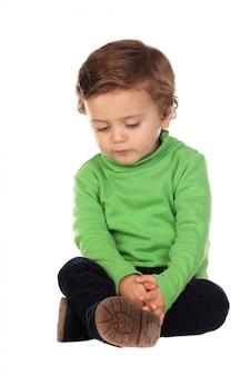 Linda criança de dois anos de idade vestindo camisa verde