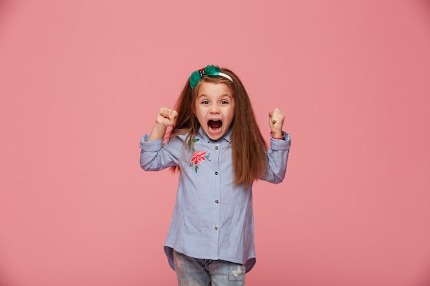 Linda criança do sexo feminino no aro de cabelo e roupas da moda, cerrando os punhos, gritando com felicidade e admiração