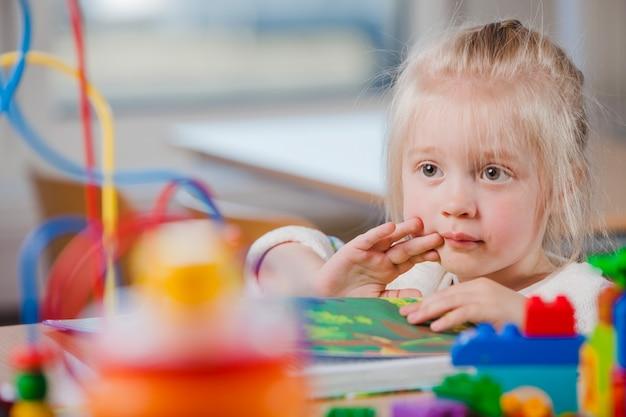 Linda criança em idade pré-escolar olhando para longe