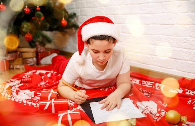 Linda criança escrevendo uma carta do papai noel perto da árvore de natal, ano novo
