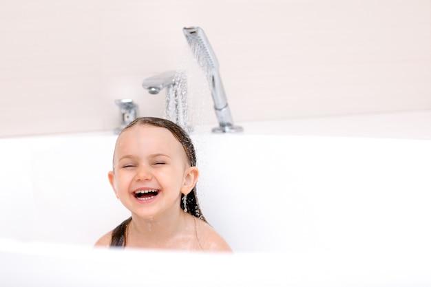 Linda criança feliz e sorridente tomando banho sob o conceito de higiene e cuidados de saúde de crianças aquáticas
