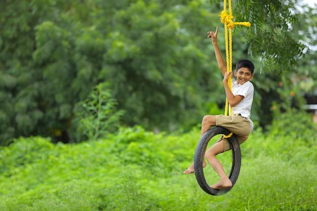 Linda criança indiana sentada em um balanço de pneu