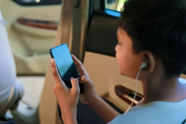 Linda criança indiana sentada no carro usando um smartphone e um gadget de fones de ouvido
