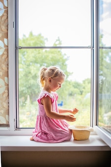 Linda criança loira de vestido rosa sentado perto de uma grande janela aberta no peitoril da janela de uma grande janela em casa e brincando com um chapéu e miçangas