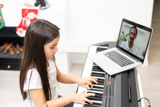 Linda criança menina tocando piano com decoração de natal no fundo. celebração de natal durante a pandemia