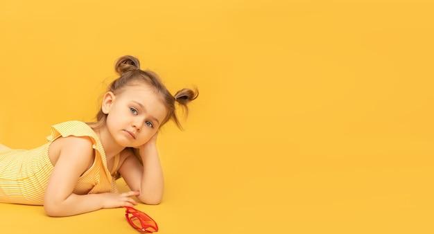 Linda criança menina vestida com um maiô amarelo posando em fundo amarelo do estúdio
