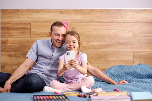 Linda criança mostrando algo engraçado no smartphone para o pai, eles se sentam juntos, aproveitando o tempo livre nos fins de semana