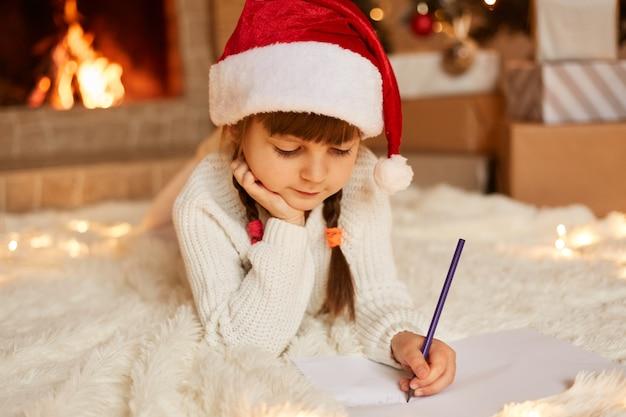 Linda criança pensativa com chapéu de papai noel festivo vermelho e suéter branco deitado no chão macio e escrevendo uma carta para o papai noel, fazendo a lista de presentes.