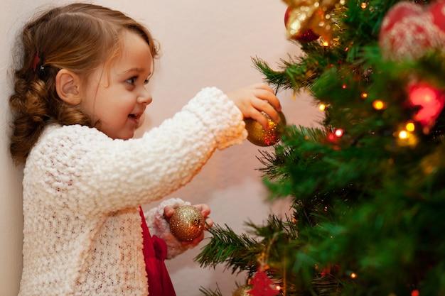 Linda criança pequena perto de árvore de natal.