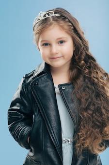 Linda criança pequena tem olhos azuis, longos cabelos escuros, mantém as mãos nos bolsos da jaqueta de couro