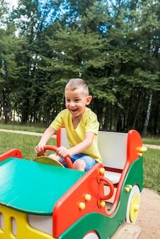 Linda criança rindo brincando em um slide em um playground lá fora, sob o sol de verão.