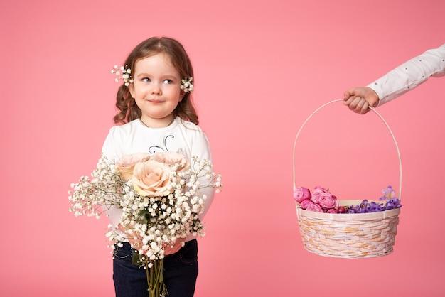 Linda criança segurando um buquê de flores de primavera e olhando para a mão que segura a cesta com flores no lado esquerdo