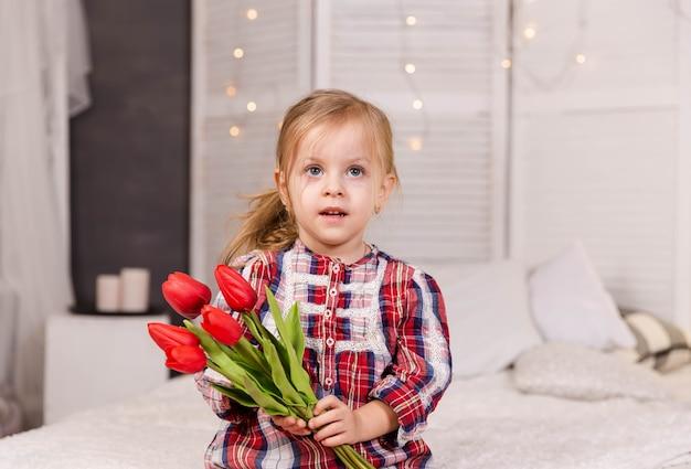 Linda criança segurando um buquê de tulipas