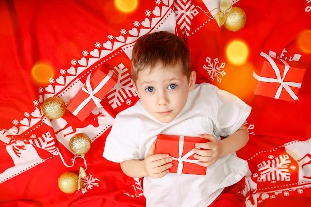 Linda criança segurando um presente de natal, garotinho loiro deitado no chão